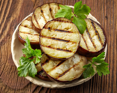 grilled eggplant slices and green parsley on wooden table