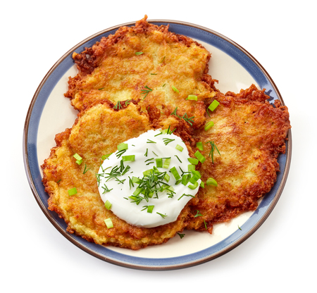 fried foods: plate of potato pancakes with sour cream and spring onions isolated on white background, top view