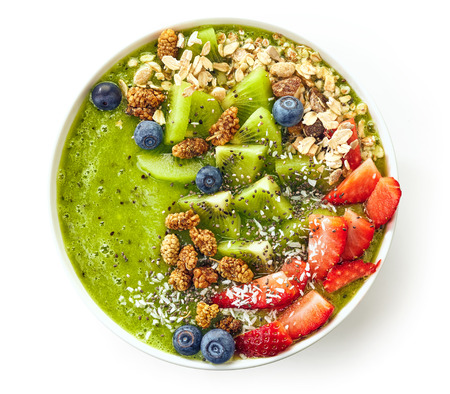 breakfast kiwi smoothie bowl topped with oat flakes and berries isolated on white background, top view 免版税图像
