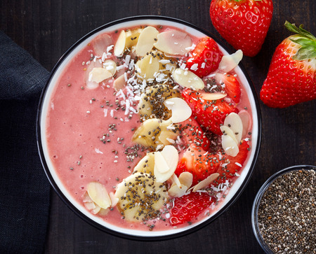 bowl of breakfast smoothie on dark wooden table, top view