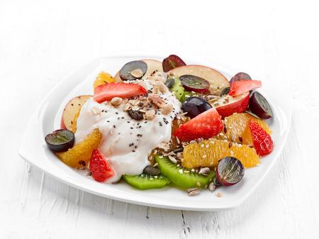 ensalada de frutas: plato de ensalada de frutas y bayas con yogur en la mesa de madera blanca Foto de archivo