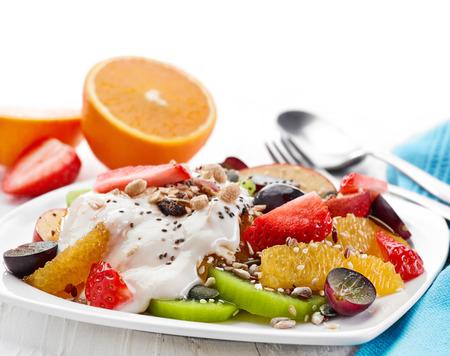 ensalada de frutas: plato de ensalada de frutas y bayas en la mesa de madera blanca
