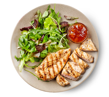 Green salad and grilled chicken fillet on plate isolated on white background, top view