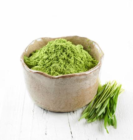 cebada: tazón de polvo de hierba de trigo verde en la mesa de madera blanca
