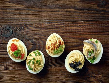 キャビアとアンチョビ、トップ ビューで飾られたぬいぐるみ卵が木製のテーブルの上