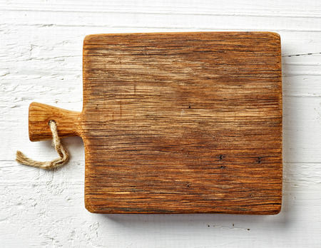 Cutting board on white wooden table, top view