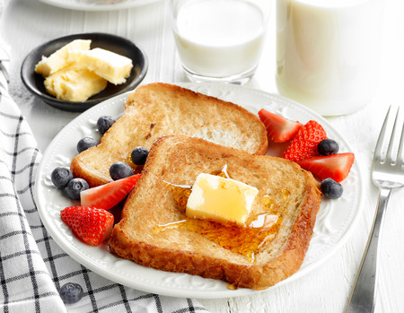 French toast with butter and honey on white plate Stockfoto
