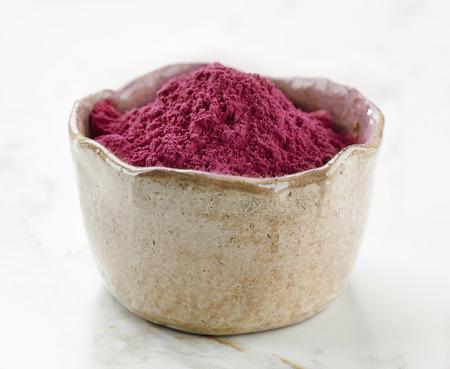 remolacha: tazón de polvo de raíz de remolacha en la mesa de la cocina