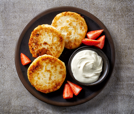 cottage: freshly baked cottage cheese pancakes with strawberries and sour cream on dark plate, top view
