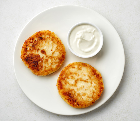cream cheese: freshly baked cottage cheese pancakes with sour cream on white plate, top view