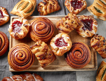 various freshly baked sweet buns on wooden cutting board, top view