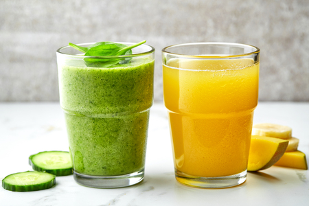 yellow green: green smoothie and yellow juice glasses on gray kitchen table Stock Photo