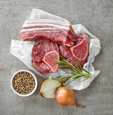assortment: various raw meat cuts and spices on gray kitchen table, top view Stock Photo