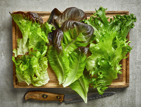various kinds of lettuce on wooden cutting board, top view