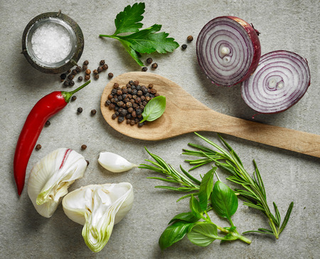 flavorings: various fresh herbs and spices on gray stone background