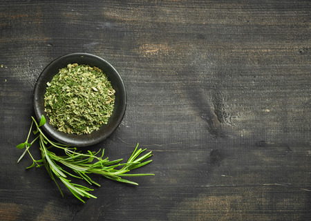 green plants: fresh and dried rosemary on dark wooden table, top view Stock Photo