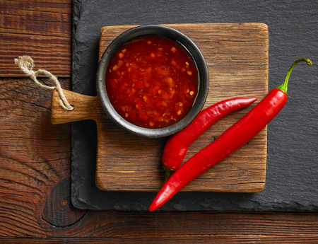bowl of red hot chili sauce on black stone background
