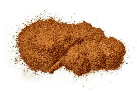 heap of ground cinnamon isolated on white background, top view