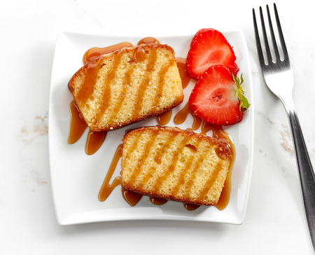 galletas: biscuit cake slices decorated with caramel sauce and strawberries on white plate, top view