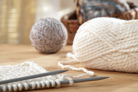 knitting: knitting needles and yarn on wooden table, still life photo with soft focus Stock Photo