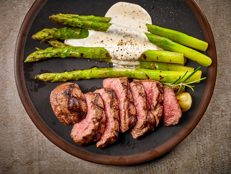 portion of sliced beef steak and asparagus on dark plate, top view Stockfoto