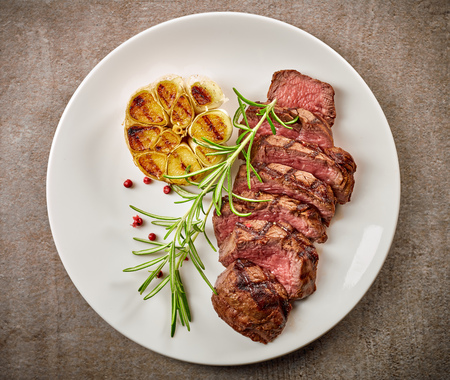 grilled sliced steak and rosemary on white plate, top view