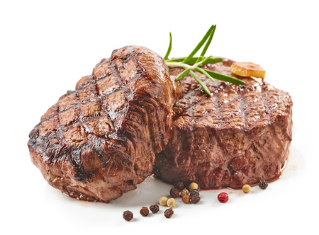 grilled beef steaks with spices isolated on white background