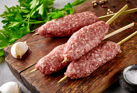 raw beef: fresh raw minced meat skewers kebabs on wooden cutting board Stock Photo