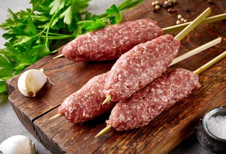 meat skewers: fresh raw minced meat skewers kebabs on wooden cutting board Stock Photo