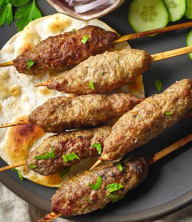 meat skewers: closeup of grilled minced meat skewers on dark plate, top view