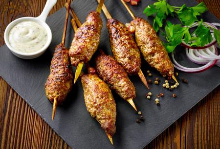 meat skewers: grilled minced meat skewers kebabs on wooden table, selective focus