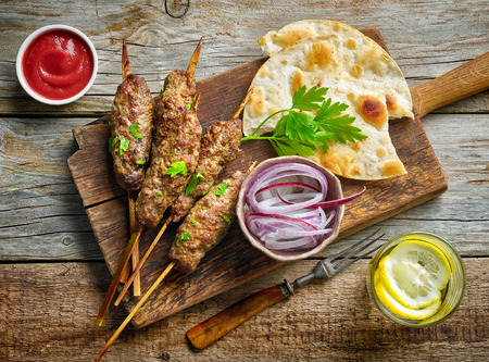 meat skewers: grilled minced meat skewers kebabs on wooden table