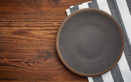 picnic cloth: napkin and dark plate on brown wooden table, top view
