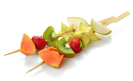 brochetas de frutas: bayas frescas y trozos de fruta en los pinchos de madera aisladas sobre fondo blanco