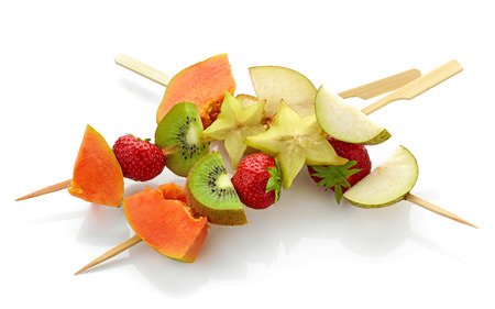skewers fruit: fresh berries and fruit pieces on wooden skewers isolated on white background