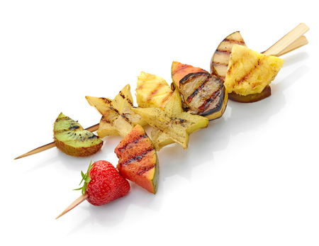 brochetas de frutas: grilled fruit pieces on wooden skewer isolated on white background