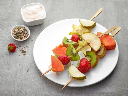 brochetas de frutas: fresh berries and fruit pieces on wooden skewers