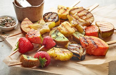 brochetas de frutas: Vaus trozos de fruta a la parrilla en brochetas de madera