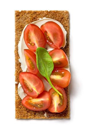 cream cheese: crispbread with cream cheese and tomato pieces isolated on white background, top view