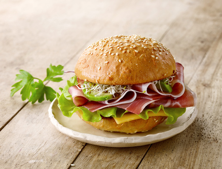 breakfast sandwich with smoked meat on wooden table Standard-Bild