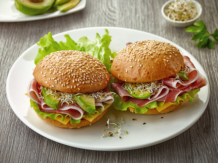 breakfast sandwiches with smoked meat and avocado on white plate