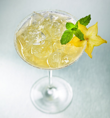 star fruit: glass of iced cocktail decorated with mint and star fruit slice, selective focus