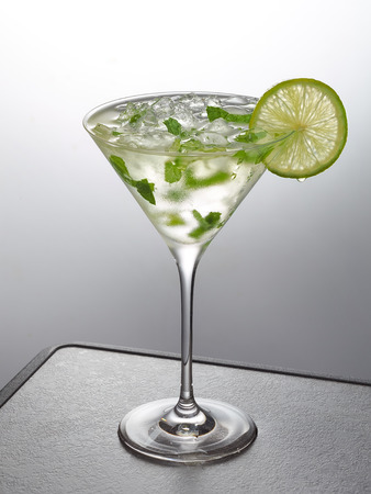 glass of iced mint and lime cocktail on gray table