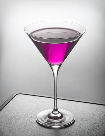 lillac: glass of violet cocktail on gray table