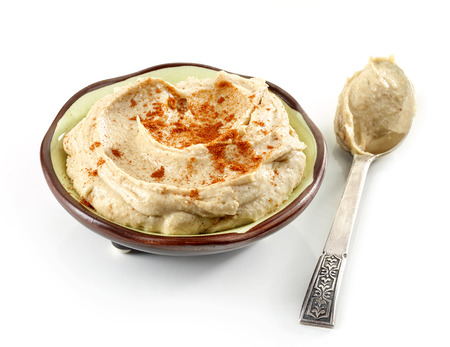 humus: bowl of hummus and silver spoon isolated on white background