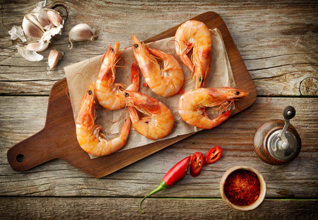 wooden board: roasted prawns on wooden cutting board, top view
