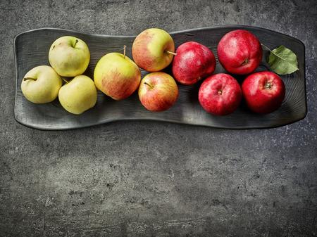 manzana roja: various fresh apples on black decorative plate, top view Foto de archivo