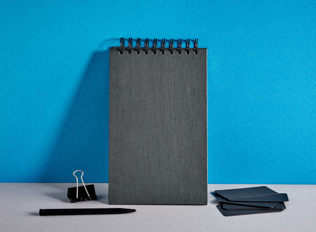notebook paper background: black notebook and visit cards on colorful paper background Stock Photo