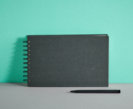 notebook paper background: black notebook and pen on colorful paper background