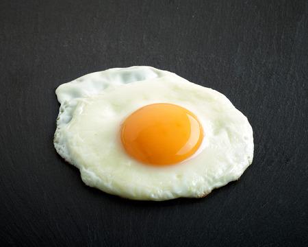 fried egg on black stone background
